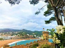 Landscape, sea, trees, flowers and medieval tower in Tossa de Mar, Spain royalty free stock photography
