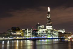 A landscape view of The Shard at night. A landscape view of The Shard in London at Night sitting behind City Hall Stock Image
