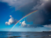 Landscape view on sky with rainbow at sea. Royalty Free Stock Image