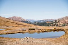 Landscape view of snow capped mountains and a pond at Independence Pass near Aspen, Colorado. Landscape view of snow capped mountains and a pond at Independence stock photography