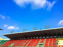 Landscape view of the soccer or football stadium. And row of red seats  on blue sky background Stock Image