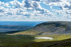 Landscape view of the Swedish northern highlands. Beautiful sunny summer view of the Highlands in Northern Sweden, with a small lake in the valley and a bright royalty free stock photography