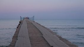 Landscape view of tranquil sunrise on the sea with wooden pier looping stock footage