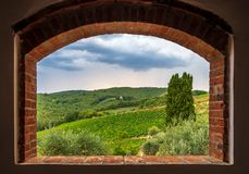 Landscape view of vineyards from the brick window, Tuscany, Italy stock photography