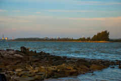 Landscape view of the water in the evening pipe with the fire on the horizon, city Bintulu, Borneo, Sarawak, Malaysia. Pantai Tema. Landscape view of the water Stock Photography