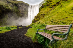 Landscape view of wild Skogafoss waterfall and bench Royalty Free Stock Photography