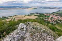 Landscape of village from castle on hill. Lake in foreground. Dramatic sky. stock photos