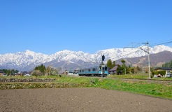 Landscape of the village of Hakuba. JR Oito line and Shirouma mountains in the village of Hakuba, Nagano, Japan Royalty Free Stock Image