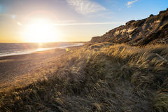 Landscape vivid sunset over beach and cliffs with added lens fla Stock Images
