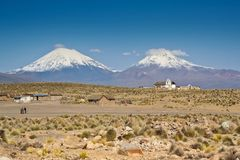 Landscape with Volcanos. Small village at the foot of Parinacota volcano in South America - Peru Royalty Free Stock Photo