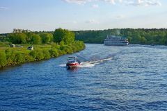 Landscape with Volga river, motor boat and cruise ship on a sum. Landscape with Volga river banks, motor boat and cruise passenger ship on a summer evening stock images