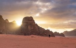 Landscape of Wadi Rum desert in sunrise with a man walking alone, and sunlight through stone mountain. Travelling and adventurous. Landscape of Wadi Rum desert royalty free stock photography