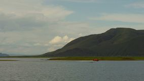Landscape with water and mountains. Coast guard floats in rubber boat stock video footage