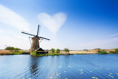 Landscape with water pumping windmill Royalty Free Stock Photos