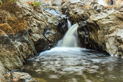 Landscape with a waterfall in a summer day. Stock Images