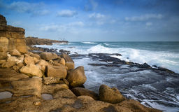 Landscape of waves crashing onto rocks during beautiful Winter's Stock Images