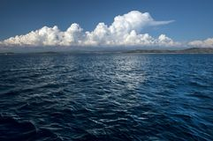 Rippling sea surface and white cloud. Landscape with wavy sea surface and white cloud over coastline stock photo
