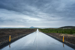 Landscape with a wet road in Iceland. Wet road after the rain. Stormy sky with dark clouds. Near Lake Myvatn, Iceland Stock Images