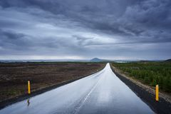Landscape with a wet road in Iceland. Landscape with a terrible dark stormy sky. Wet road in Iceland. Bad weather. Near Lake Myvatn Stock Photos