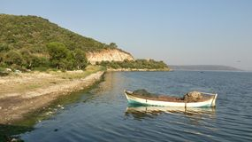 Landscape with white boat. White boat near the seaside with reflection and big rock on background Royalty Free Stock Photo