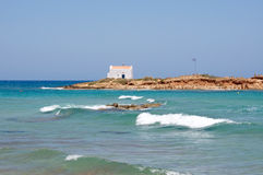 Landscape of a white church on the rocks at Malia beach, Crete, Greece Royalty Free Stock Photography