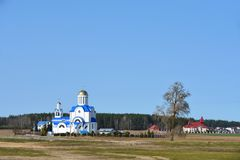 The landscape of the white church stands full on the edge of the village in the spring stock photos