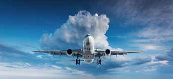 Landscape with white passenger airplane is flying in the blue sk stock photos
