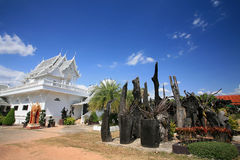 Landscape of white temple architecture and garden. Ornament: beautiful landscape of white temple architecture and plant environment against clear sky at wat Tham Stock Images
