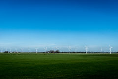 Landscape with wind energy turbines. Renewable energy - Wind energy turbine / modern wind mill against blue sky background Stock Photo