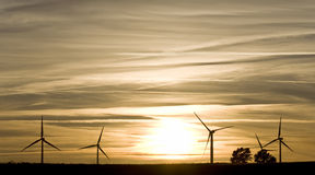 Landscape with wind turbines. Silhouettes of wind turbines on sunset sky background Royalty Free Stock Photography