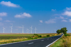 Landscape of wind turbines and an asphalt road stretching into t Royalty Free Stock Photo