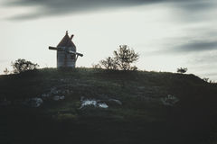 Landscape of a windmill on a hill. A gloomy landscape of an old abandoned windmill on a stony hill Stock Photo