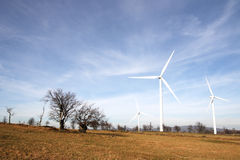 Landscape with windmills. View of landscape with several windmills against blue sky generating power Royalty Free Stock Images