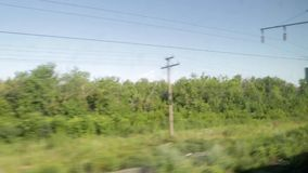 The landscape from the window of a moving train. Summer Sunny day, green trees, power line poles.  stock video footage