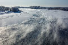 Landscape winter river freezes with frost, steam rises over the river on a Sunny day.  royalty free stock image