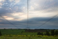 Perspective of wires in the cloudy sky above the grass royalty free stock photo