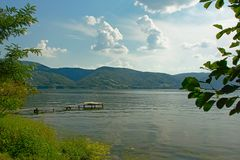 Landscape witj river Danube with old wooden pier and mountains in the background stock photos