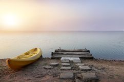 Landscape wood shore with kayak boat at island in sunrise time. Stock Photography