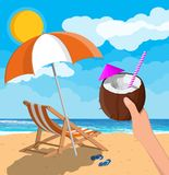 Landscape of wooden chaise lounge, cocktail. Coconut with cold drink in hand. Landscape of wooden chaise lounge, umbrella, flip flops on beach. Sun with Stock Images