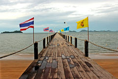 Landscape of wooden deck bridge to pier. Landscape of wooden deck bridge to the boat along with flags Royalty Free Stock Images