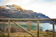 A landscape of a wooden fence at first shot and snow on the peaks of the mountains and the blue water of the lake in the afternoon. Horizontal photo royalty free stock photos