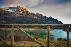 a landscape of a wooden fence at first shot and snow on the peaks of the mountains and the blue water of the lake in the afternoon stock image