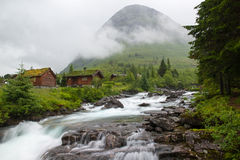 Landscape with wooden houses, river and mountain, Norway Royalty Free Stock Photo