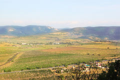 Landscape. Young vineyards, woods, mountains and valley. Railroad tracks, highway and houses Stock Photo