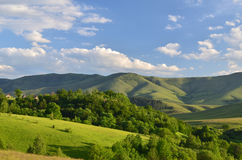Landscape of Zlatibor Mountain. Green meadows and hills under blue sky with clouds in springtime Royalty Free Stock Photography