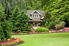 Landscaped cottage in woods. A view of a small, secluded log cottage in the woods with colorful flower landscaping and gardens Royalty Free Stock Photo