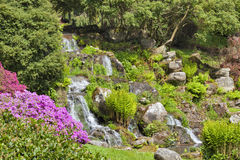 Landscaped english garden with stone waterfall in spring Royalty Free Stock Image