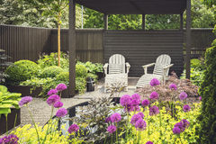 Landscaped garden with terrace. Cozy lounge furniture on landscaped garden terrace royalty free stock image
