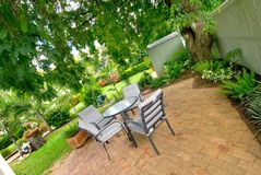 Landscaped gardens and setting. Landscaped backyard found in Australia, with your big shady trees, lush green grass and plenty of garden beds with a patio Royalty Free Stock Image