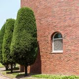 Landscaped green trees in front of a red brick royalty free stock images